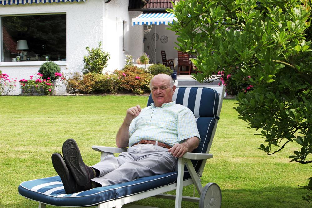 Rentner genießt seinen Lebensabend entspannt auf einer Gartenliege im Schatten eines Baumes vor seinem Eigenheim.